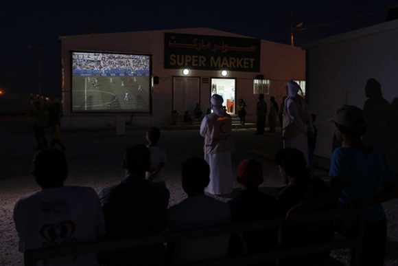 UAE Red Crescent members and Syrian refugees watch the World Cup soccer match between Argentina and Switzerland on a large screen after taking their meals for iftar during Ramadan at the Mrajeeb Al Fhood refugee camp