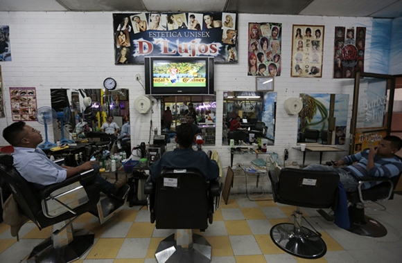 People watch the 2014 World Cup opening soccer match in a barber shop in Guatemala City