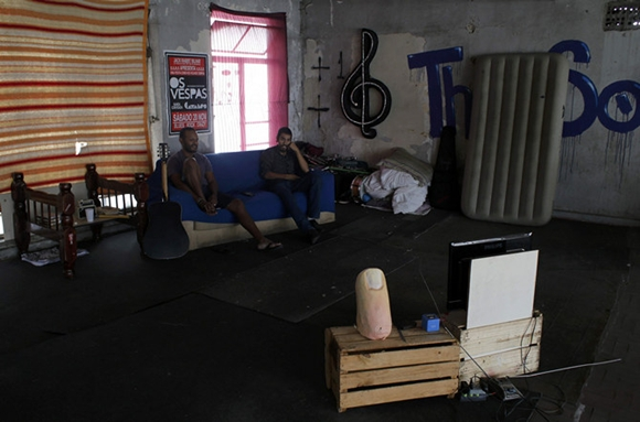Grey and Alan, local dwellers, who live as squatters in an abandoned office building, watch a soccer match between Australia and the Netherlands in the centre of Sao Paulo