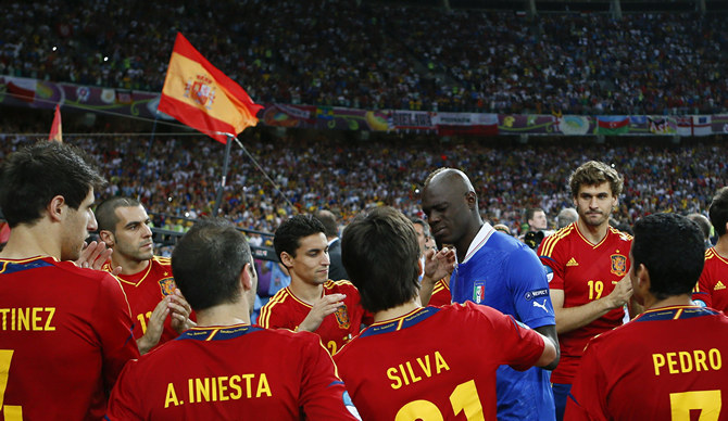Spain players comfort Italy's Balotelli after defeating Italy to win the Euro 2012 final soccer match at the Olympic stadium in Kiev