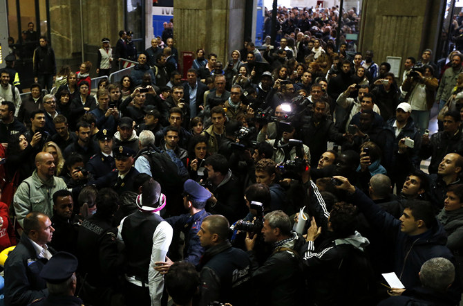 Italy's Mario Balotelli is escorted as he arrives with the national soccer team at the Railway Central station in Milan