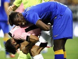 Juventus' Pogba helps Palermo's Pisano during their Italian Serie A soccer match in Turin