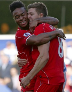 Liverpool's Raheem Sterling celebrates with Steven Gerrard after his cross led to the winning own goal during their English Premier League soccer match against Queens Park Rangers at Loftus Road in London