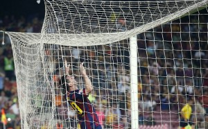 Barcelona's Messi reacts while hanging from the net after missing a goal against Eibar during their Spanish first division soccer match at Camp Nou stadium in Barcelona