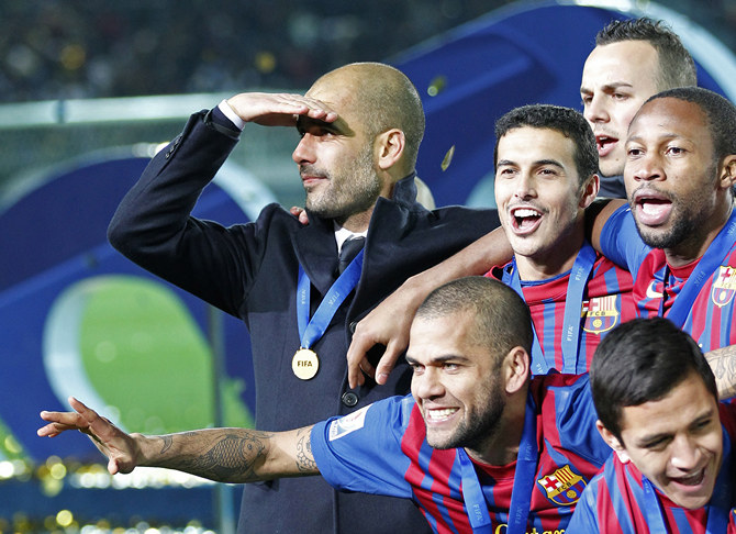 Coach Guardiola of Spain's Barcelona celebrates with players on the podium after their win in the Club World Cup final soccer match against Brazil's Santos in Yokohama