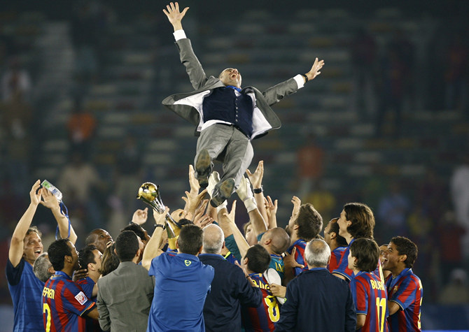 Members of Barcelona's soccer team throw coach Pep Guardiola in the air after defeating Estudiantes in their FIFA Club World Cup final in Abu Dhabi