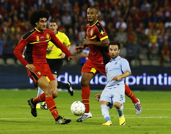 France's Valbuena is challenged by Belgium's Fellaini and Kompany during their international friendly soccer match at the King Baudouin stadium in Brussels