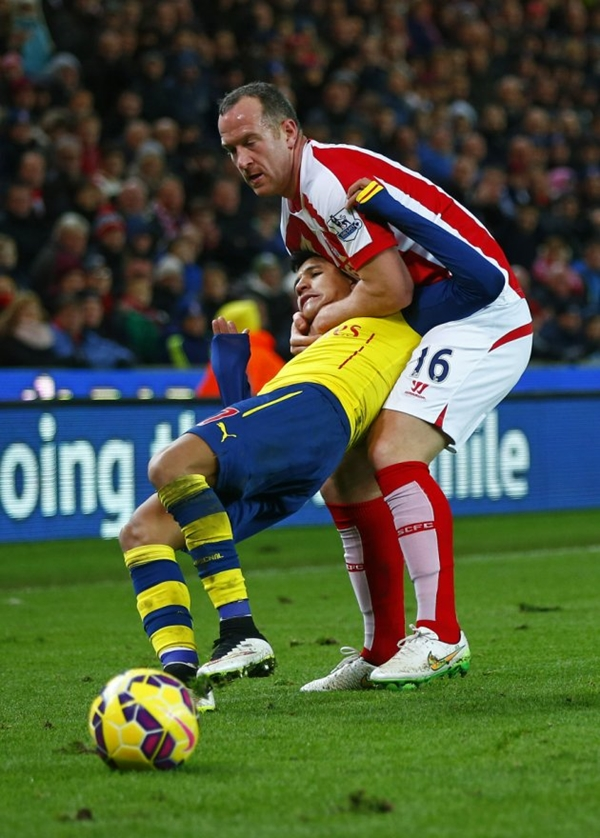 Stoke City's Charlie Adam gets a yellow card for a foul on Arsenal's Alexis Sanchez during their English Premier League soccer match in Stoke