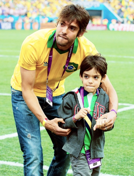 Kaka with his son walks along the pitch before kick off