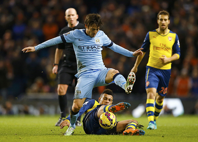 Arsenal's Francis Coquelin is challenged by Manchester City's David Silva during their English Premier League soccer match in Manchester
